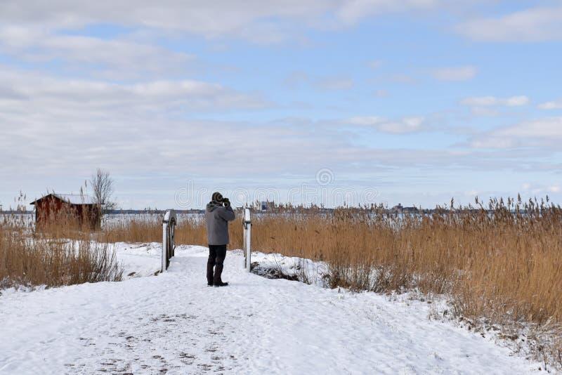 Birdwatcher en un paisaje del invierno imagen de archivo