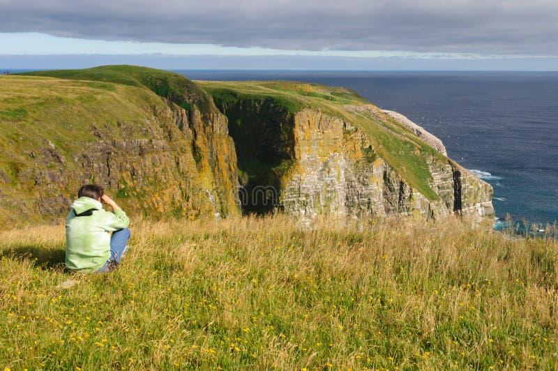 Birdwatcher som ser fåglar på kust- klippor royaltyfria foton