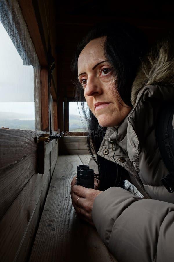 Birdwatching, uma mulher com binóculos imagem de stock royalty free