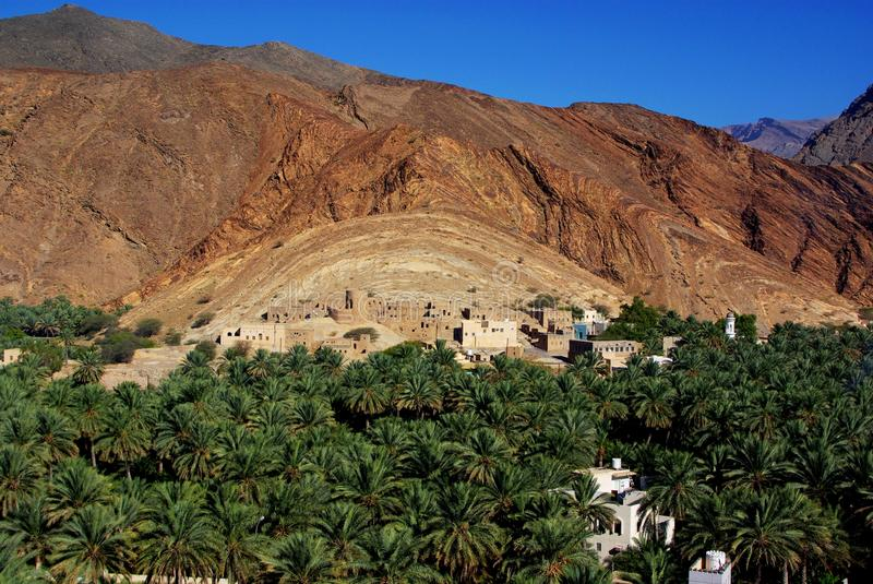 Birkat Al Mawz View. View of the stunning Birkat Al Mawz, featuring an oasis of date palms and ancient buildings beneath intimidating desert mountains (Oman stock photos