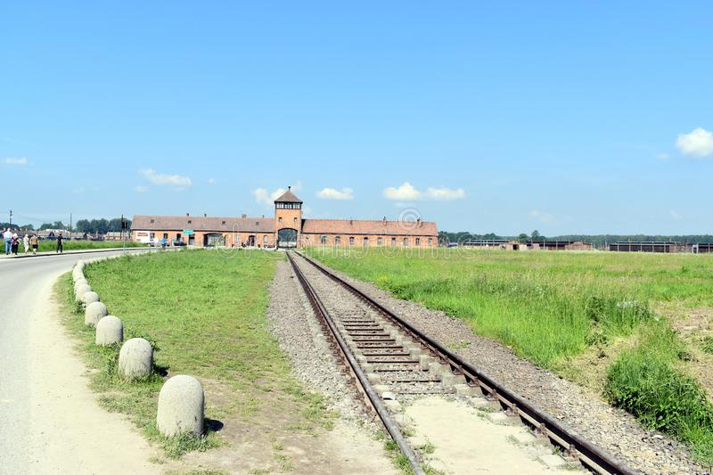 The railway track going into the main entrance of Birkenau Concentration Camp. Birkenau/Poland-June 3, 2019: The railway track going into the main entrance of royalty free stock photos