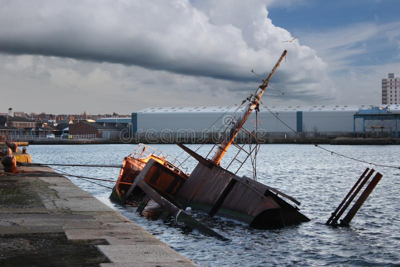 Birkenhead Sunken Ship. March 27, 2010 – Birkenhead Dock, Liverpool, England, United Kingdom. An old rusty ship sunken inside the harbour area, against royalty free stock image