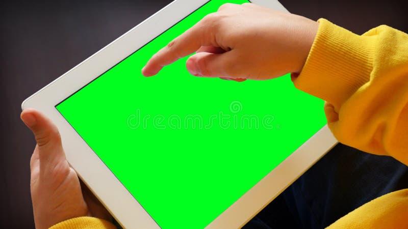 Birlando en Tablet PC, mano de un niño fotografía de archivo
