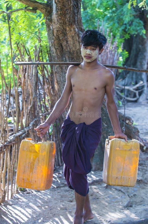 Birmańscy Średniorolni przewożenie klingerytu wiadra wypełniali z wodą obrazy stock