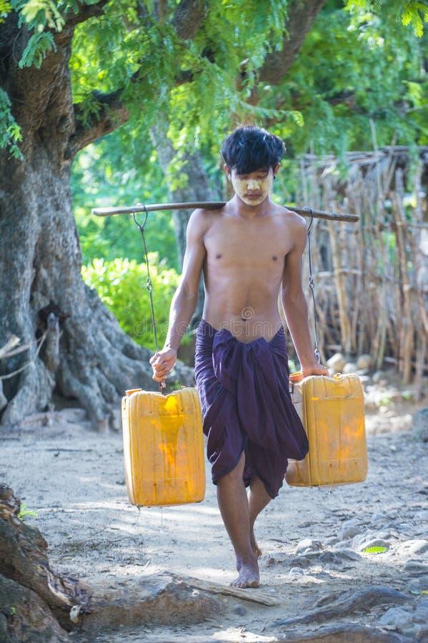 Birmańscy Średniorolni przewożenie klingerytu wiadra wypełniali z wodą obraz stock