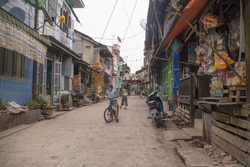 Birmańscy dzieci z bicyklami bawić się na ulicie, Mawlamyine, Birma, Marzec 2012: Dwa dzieciaków Birmańska sztuka na mieszkaniowe obrazy royalty free