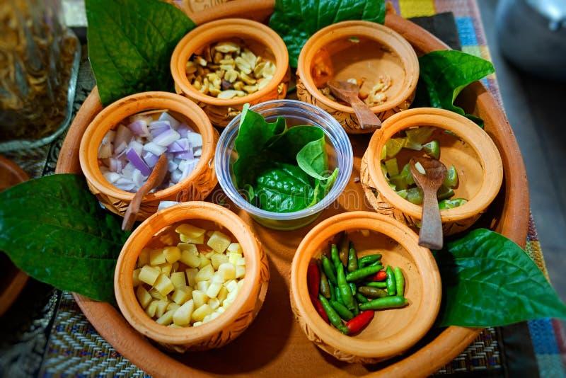 Birmańska Herbaciana liść sałatka, Lahpet w drewnianym talerzu z Dzikim betlem lub Opuszczamy na lekkim drewnianym stole w ciepły obraz royalty free