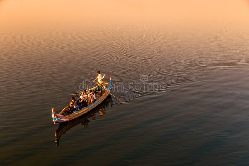 Birmaanse boatman die toerist voor sightseeing nemen bij de brug van U Bein, de Mensenmeer van Taung Tha in Amarapura, Mandalay,  stock afbeeldingen