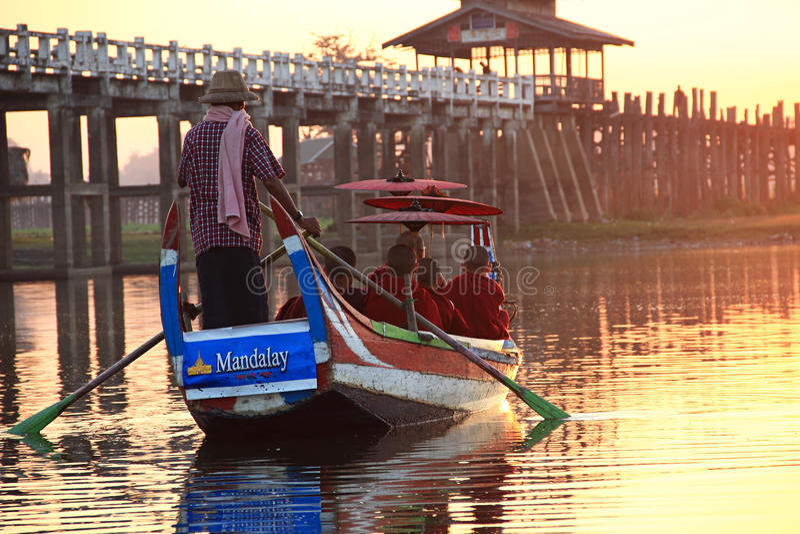 Birmaanse boatman en boeddhistische beginnerzitting in boot stock fotografie