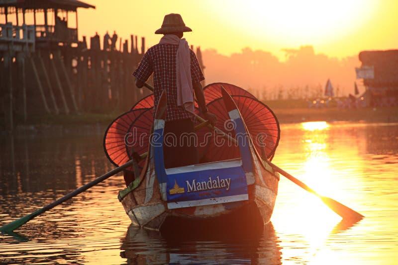 Birmaanse boatman en boeddhistische beginnerzitting in boot royalty-vrije stock afbeeldingen
