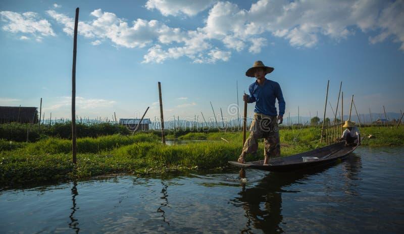 Birmaanse boatman leidt een houten boot stock fotografie