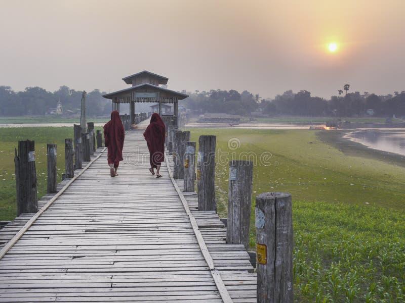 Birmaanse monniken die over de Brug van U Bein bij zonsondergang lopen royalty-vrije stock fotografie
