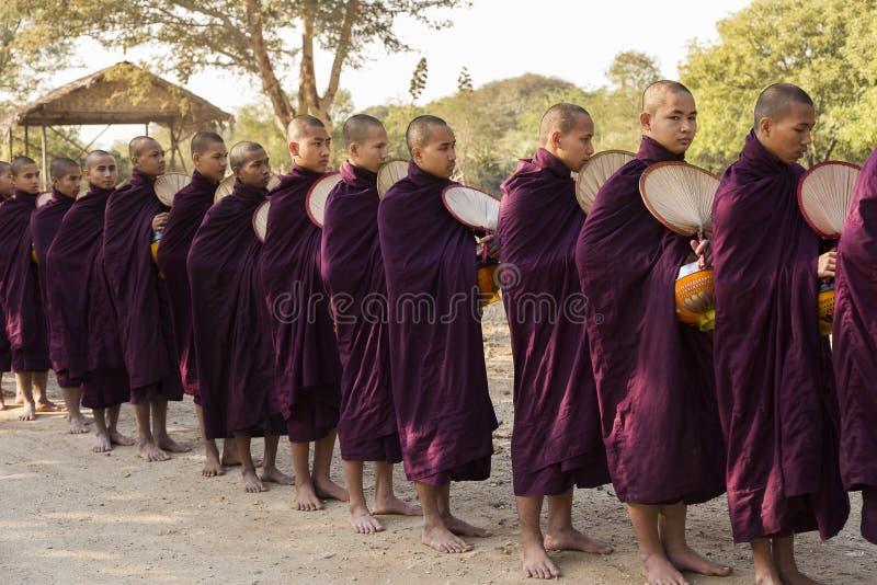 Birmaanse monniken in donkere purpere robes met kom die zich in lijn bevinden die op voedsel wachten royalty-vrije stock foto