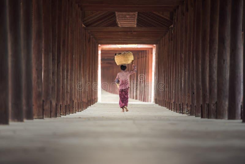 Birmaanse vrouw die bamboemand zetten stock afbeelding