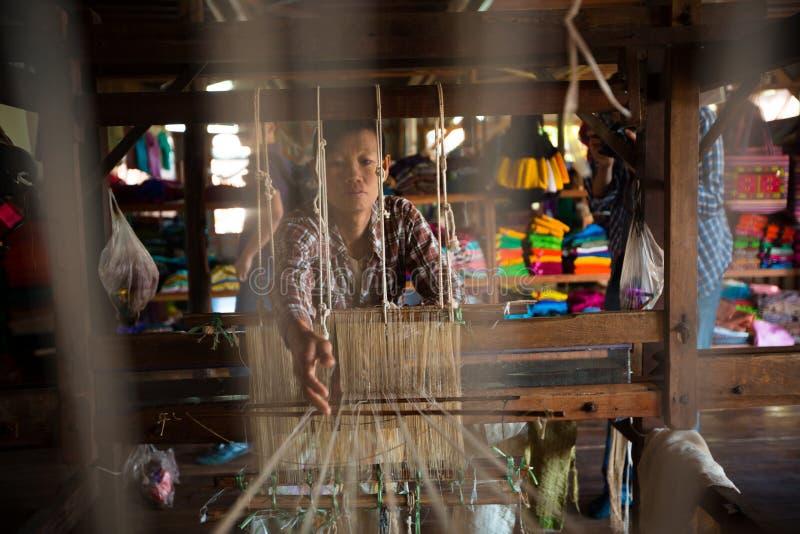 Birmanische Frau arbeitet mit Lotoswurzelthread auf einem Webstuhl stockfotos