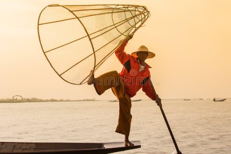 Birmanischer Fischer auf anziehenden Fischen des Bambusbootes auf traditionelle Art mit handgemachtem Netz Inle See, Myanmar (Bir stockbild