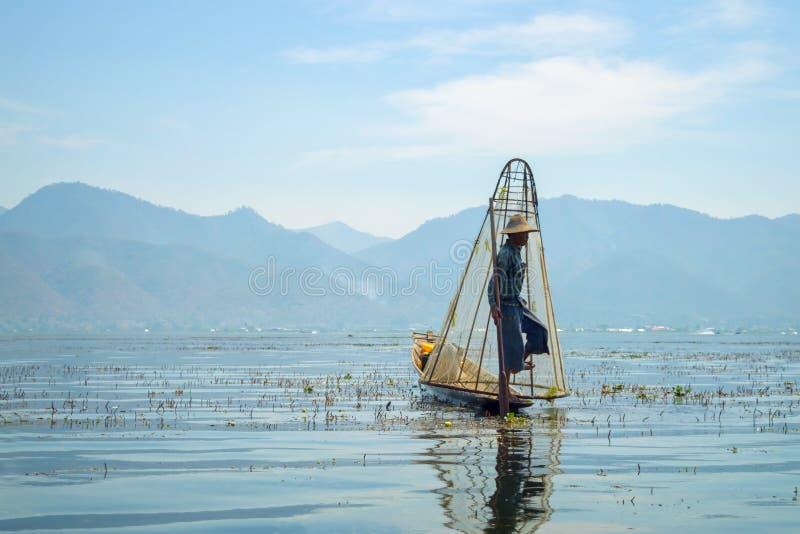 Birmanischer Fischer auf anziehenden Fischen des Bambusbootes auf traditionelle Art mit handgemachtem Netz Inle See, Myanmar Birm lizenzfreies stockfoto