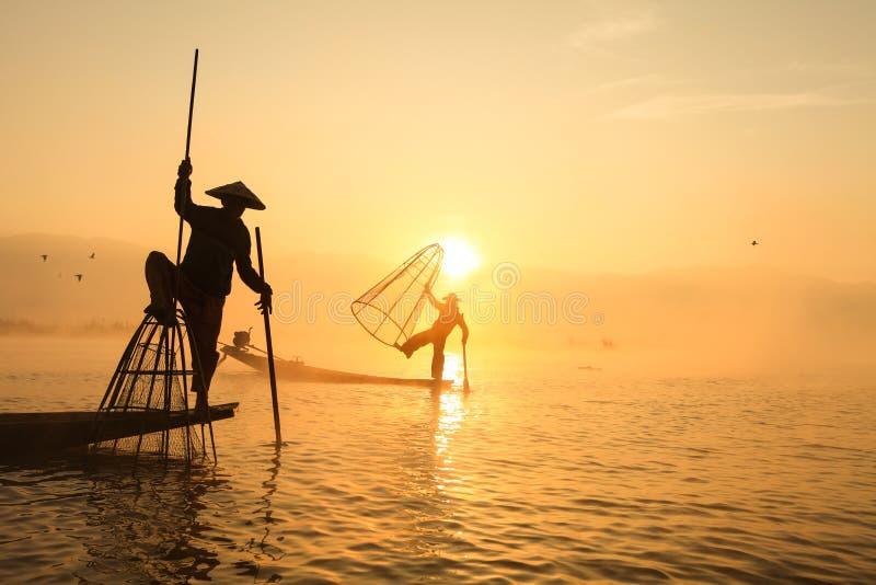 Birmanischer Fischer auf anziehenden Fischen des Bambusbootes im traditionellen wa lizenzfreies stockbild