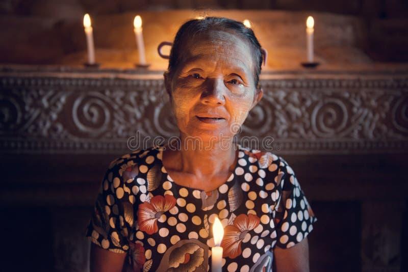 Birmanisches Frau prayingwith Kerzenlicht lizenzfreie stockfotos