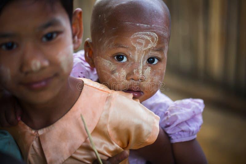 Birmanisches Kind mit traditionellem Thanaka stellen Farbenhaltungen für Porträt gegenüber stockfotos