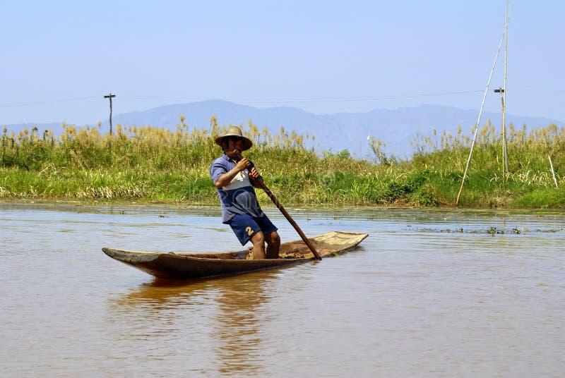 Birmese persoon in een boot op het Inle Lake stock foto