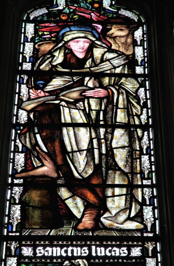 Saint Luke the Evangelist. BIRMINGHAM, UK - APRIL 24, 2013: Saint Luke the Evangelist on stained glass inside St Martin in the Bull Ring church in Birmingham royalty free stock images