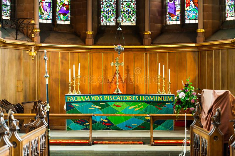 BIRMINGHAM, UK - March 2018 Chancel Area in Church for Choir and Clergy. Stained Glass and Wood Panel Wall as Backdrop. Celtic Cross and Candlestick Holder royalty free stock photos