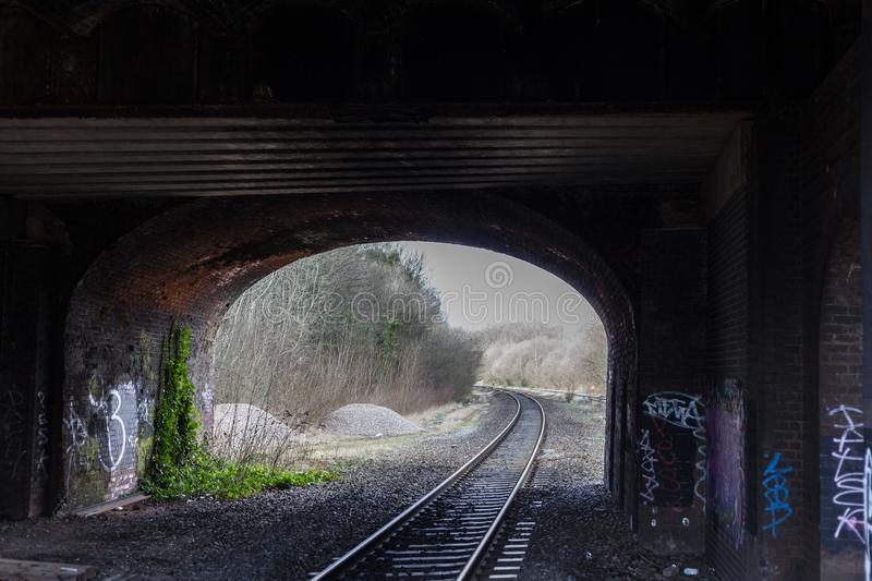 BIRMINGHAM, UK - March 2018 Railroad Track under Weathered Bridge Tunnel. Bricked Wall is Dirty and Vandalized. Gravel royalty free stock photography