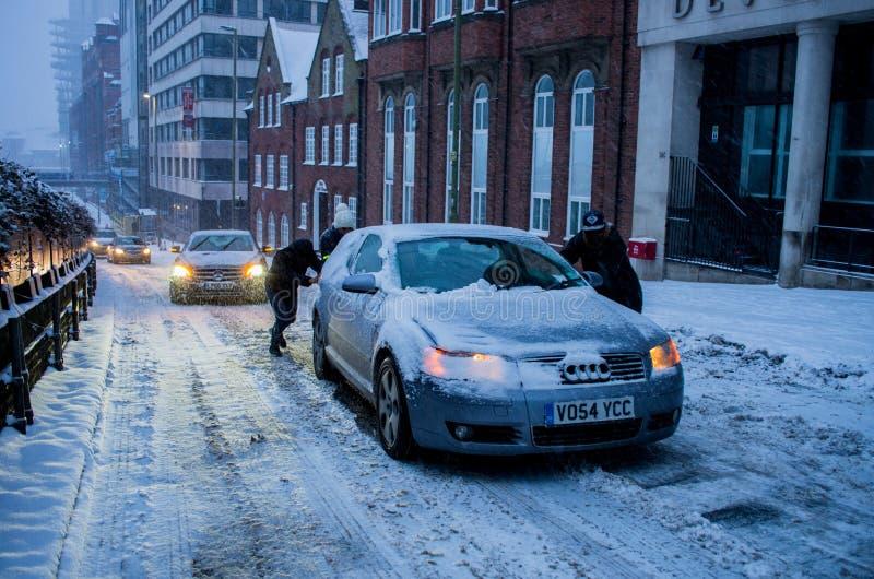Heavy snow in Birmingham, United Kingdom. Birmingham, United Kingdom - March 02 2018 : People pushing a car slipping during heavy snow in Birmingham, United royalty free stock photo