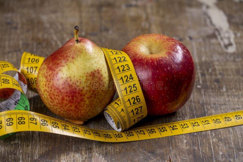 Birne und Apfel, die Arten des Übergewichts darstellen stockfoto