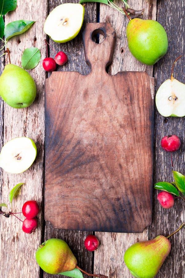 Birne und kleiner Apfel um leeres Schneidebrett auf hölzernem rustikalem Hintergrund Beschneidungspfad eingeschlossen Feld Herbst lizenzfreie stockbilder