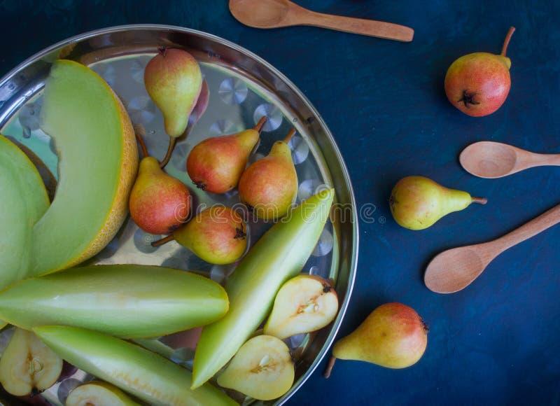 Birne und Melone auf einem dunklen Hintergrund stockfoto