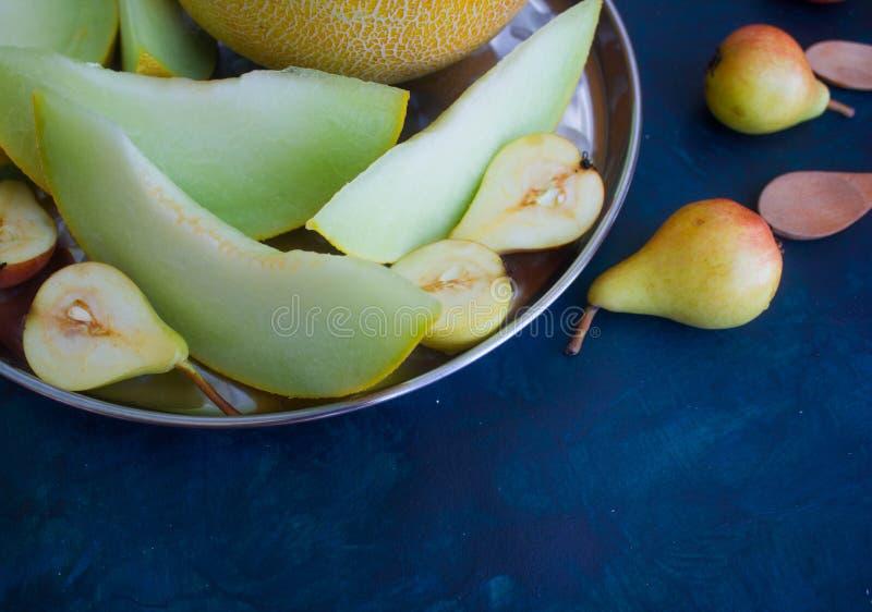 Birne und Melone auf einem dunklen Hintergrund lizenzfreies stockfoto