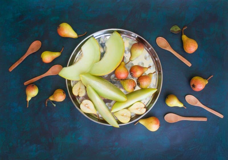 Birne und Melone auf einem dunklen Hintergrund lizenzfreie stockfotos