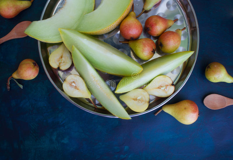 Birne und Melone auf einem dunklen Hintergrund lizenzfreies stockbild