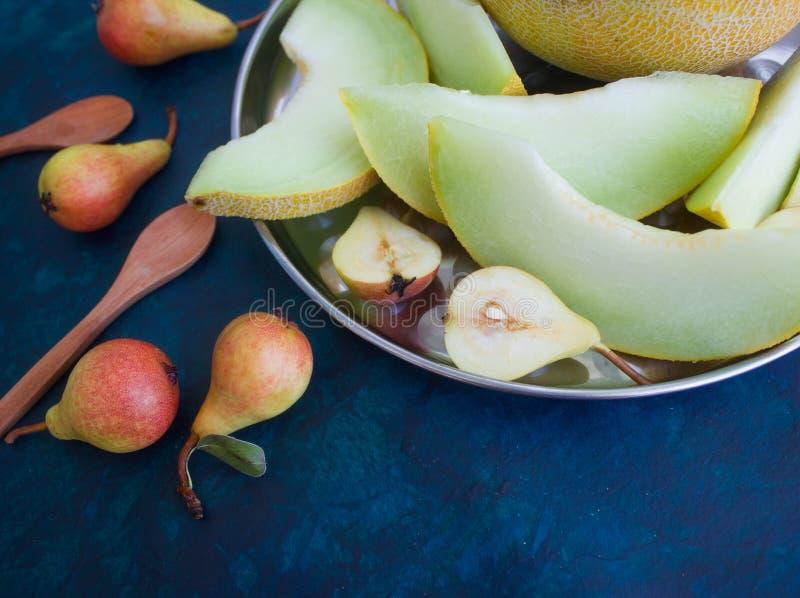 Birne und Melone auf einem dunklen Hintergrund stockbilder
