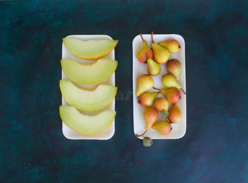 Birne und Melone auf einem dunklen Hintergrund stockfotos