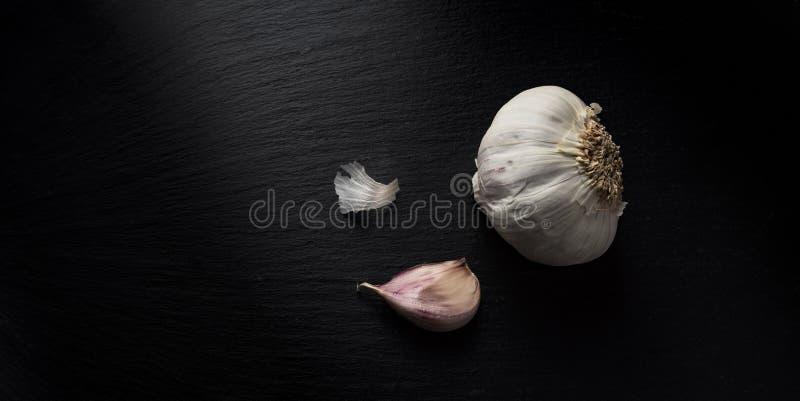 Birnen des getrockneten Knoblauchs auf schwarzer Schieferoberfläche lizenzfreies stockfoto