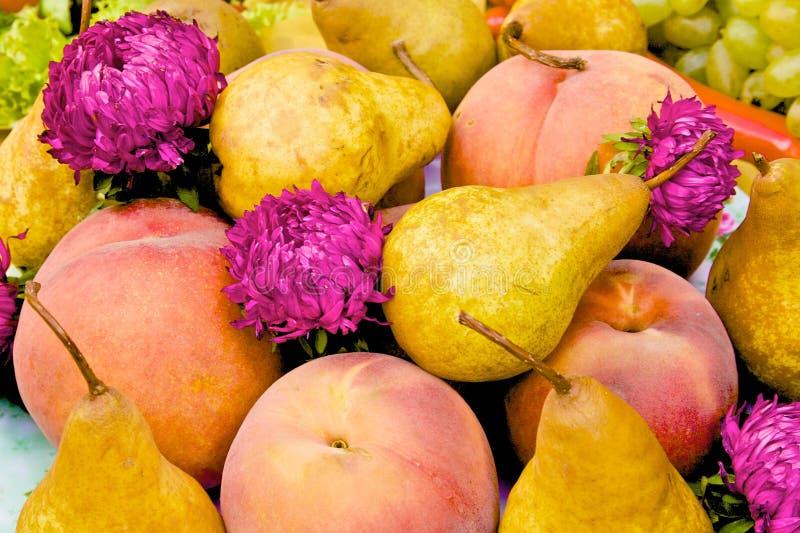 Birnen, Pfirsiche und Blumen auf Tabelle stockbilder