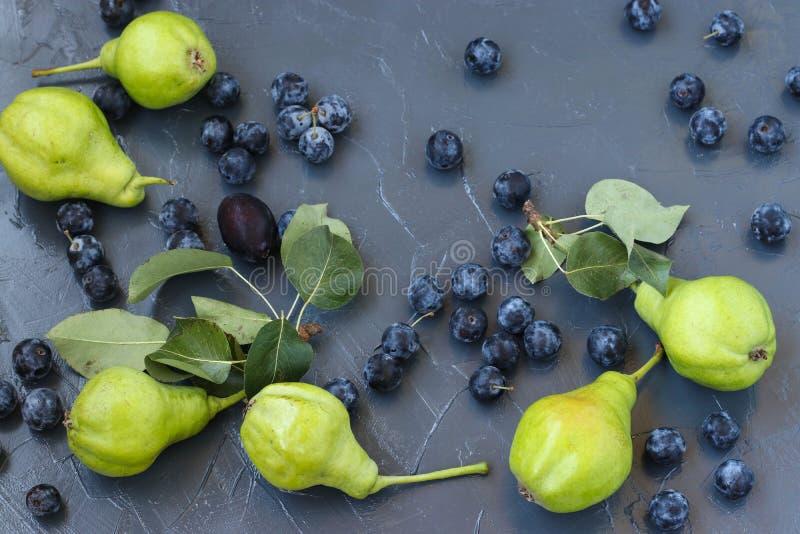 Birnen und Schlehdorn sind auf einem dunklen Hintergrund in der gelegentlichen Bestellung stockfoto