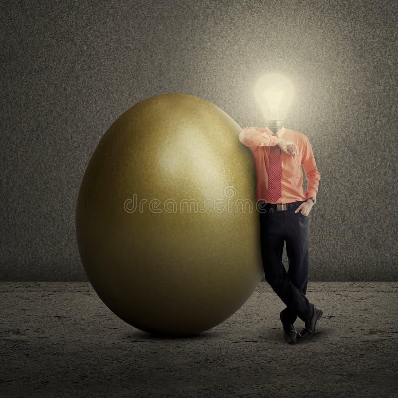 Birnenhauptgeschäftsmann, der mit goldenem Ei steht stockbild