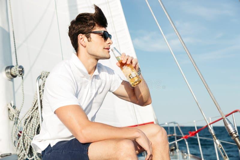 Birra bevente bella del giovane mentre riposando sull'yacht fotografia stock libera da diritti
