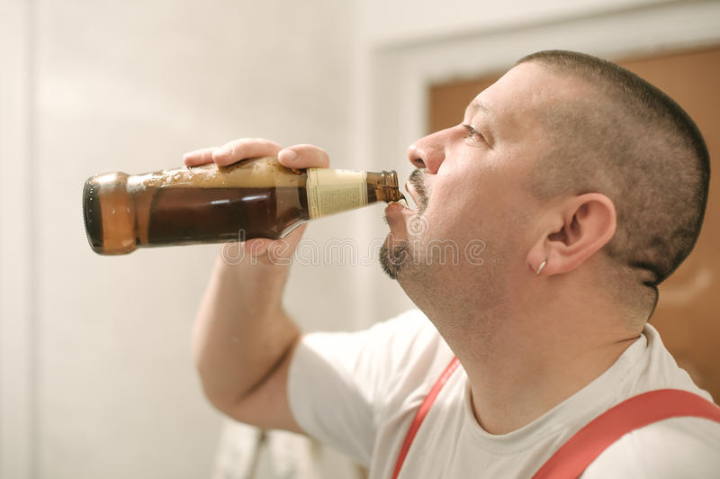 Birra bevente del lavoratore del muratore della costruzione durante la pausa di lavoro fotografia stock libera da diritti