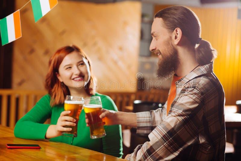 Birra bevente dell'uomo barbuto con la sua donna allegra immagine stock