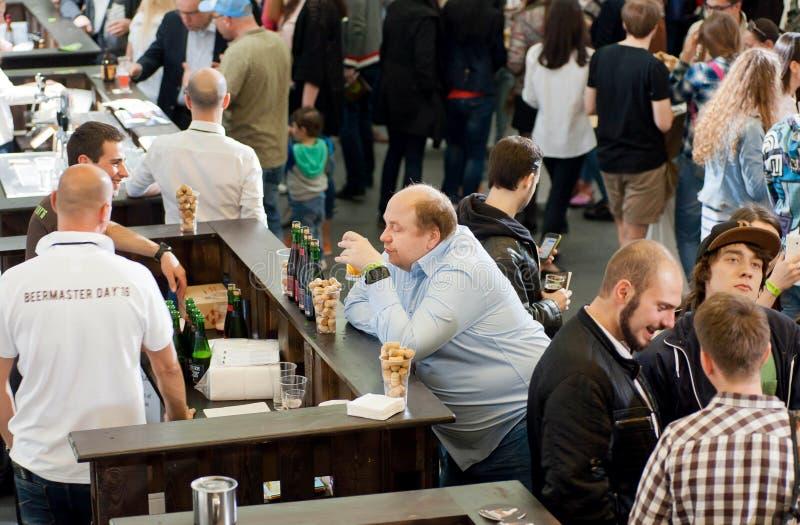 Birra bevente dell'uomo solo in folla della gente fotografia stock