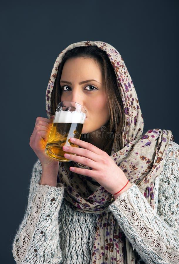 Birra bevente della ragazza graziosa dal vetro immagini stock libere da diritti