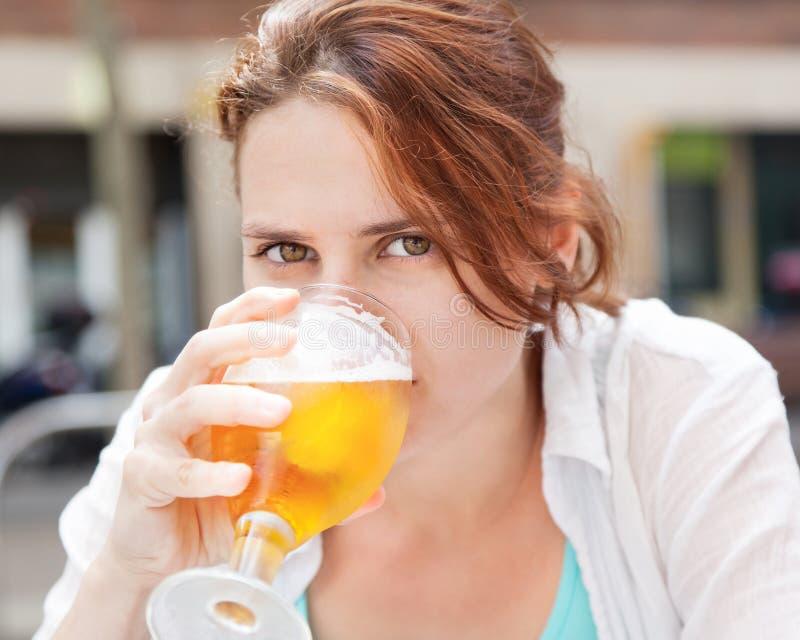 Birra bevente della ragazza graziosa dal vetro fotografia stock