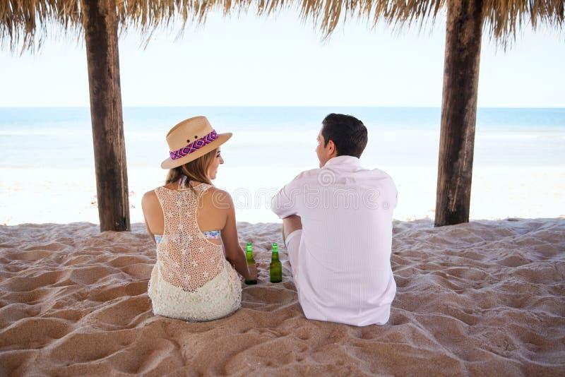 Birra bevente delle coppie alla spiaggia fotografia stock libera da diritti