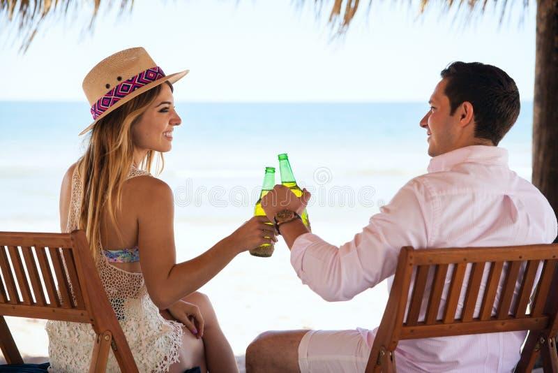 Birra bevente delle coppie alla spiaggia immagini stock
