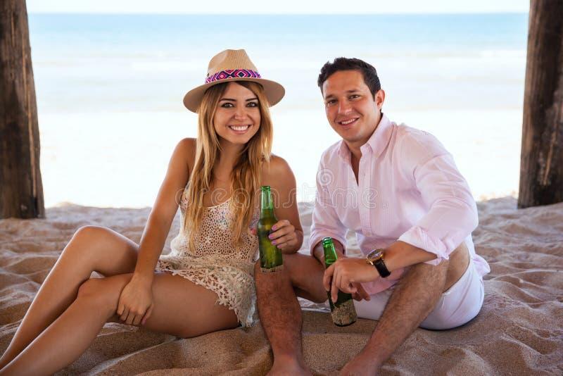 Birra bevente delle coppie ispane alla spiaggia immagine stock libera da diritti